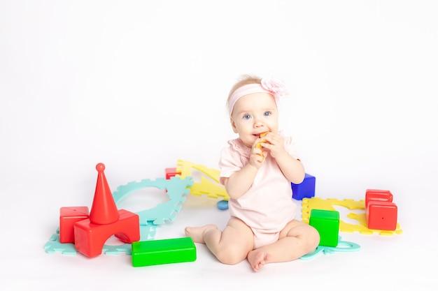 Het kind speelt met kubussen op een witte geïsoleerde achtergrond, ruimte voor tekst
