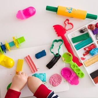 Het kind speelt met veelkleurige klei en maakt speelgoed van plasticine