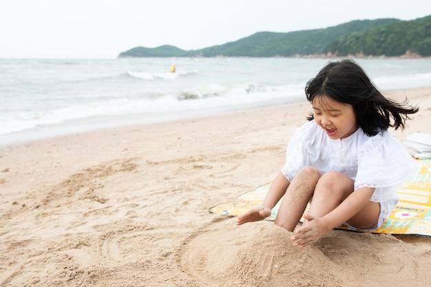 Het kind speelt met zand op het strand.