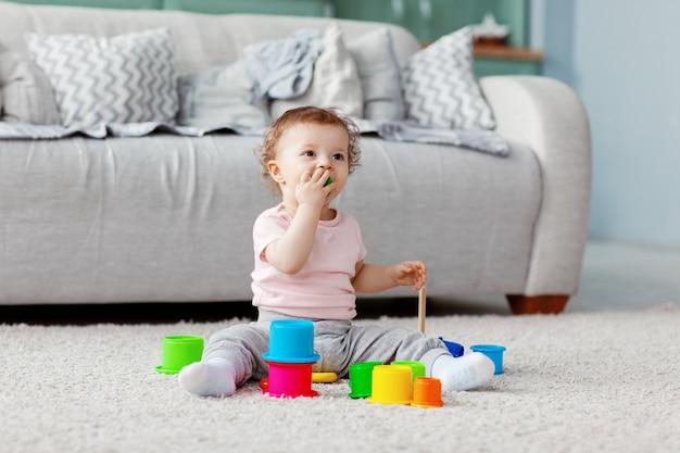 Het kind speelt op de vloer op een licht tapijt met licht speelgoed, bouwt een toren