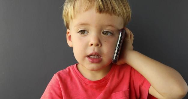 Het kind spreekt op mobiele telefoon