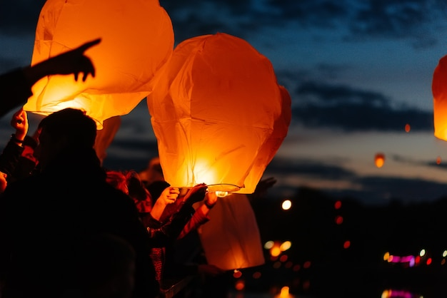 Het kind start de lantaarns in de lucht op een donkere nacht. viering, tradities van het nieuwe jaar.