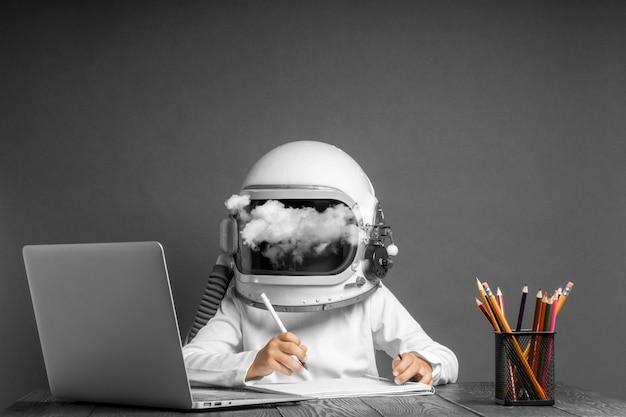 Het kind studeert op afstand op school, met een astronautenhelm op. terug naar school