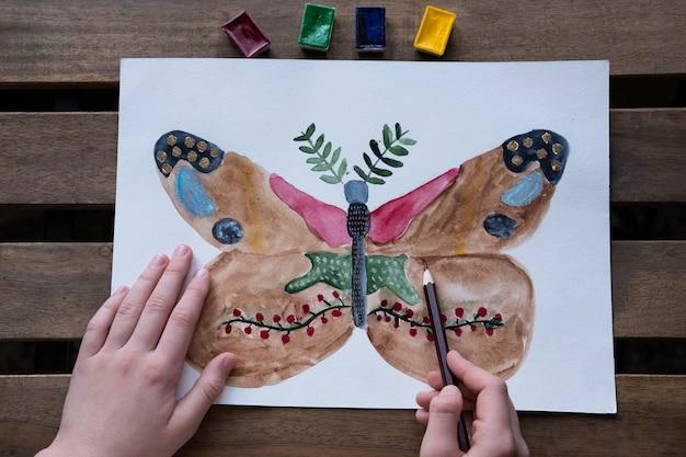 Het kind tekent een ongewoon mooie vlinder met aquarellen en potloden