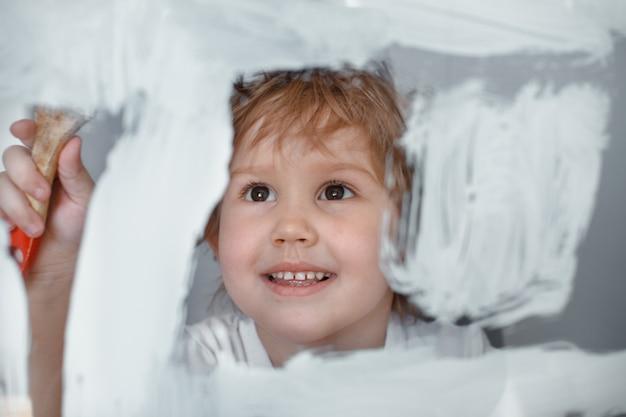 Het kind tekent een witte verf op een glazen bord. gesimuleerd scherm.