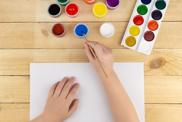 Het kind tekent en veel potloden en verf om te tekenen