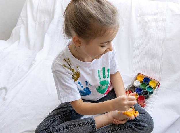 Het kind tekent met een penseel een patroon op zijn voet.