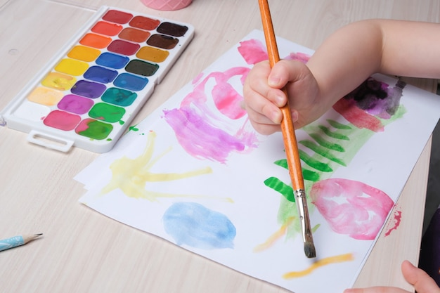 Het kind tekent met een penseel op papier