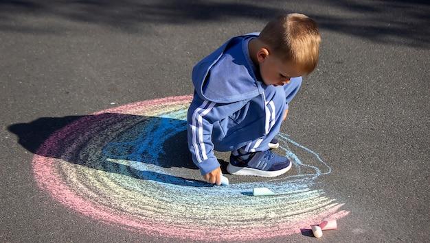 Het kind tekent met krijt de kleuren van de regenboog op het asfalt