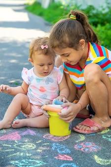Het kind tekent met krijt op het asfalt