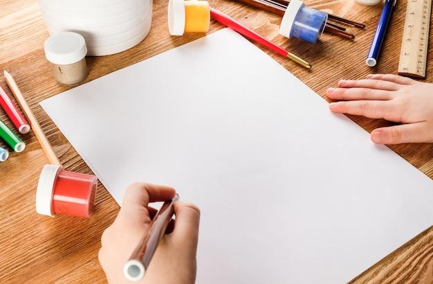 Het kind tekent met viltstiften en verf. de handen van het kind met potloden en blocnote.