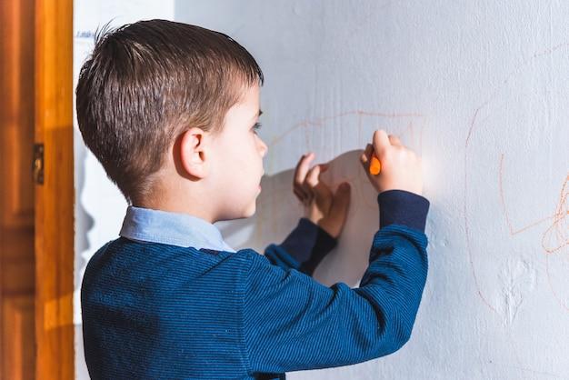 Het kind tekent op de muur met gekleurd krijt. de jongen is thuis bezig met creativiteit creativity