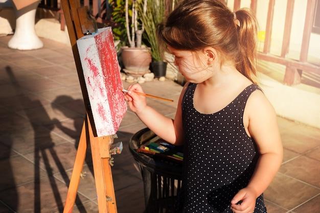 Het kind tekent op een malbert. een meisje strijkt met verf over het doek