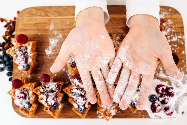 Het kind toont handpalmen met suikerpoeder