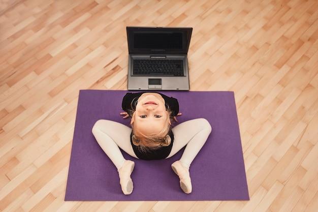 Het kind traint thuis achter een laptop