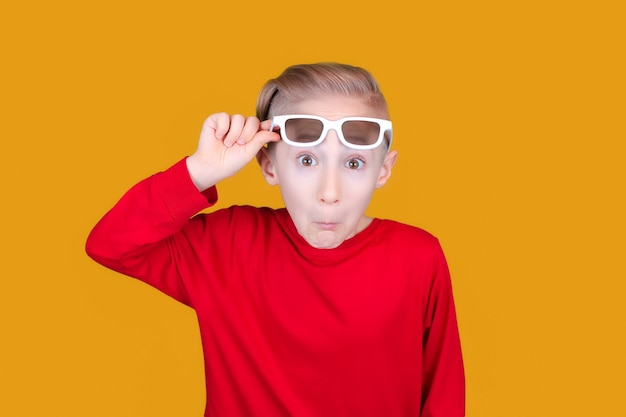 Het kind trekt aan het voorhoofd van de 3d-bril van kinderen en trekt grappige gezichten