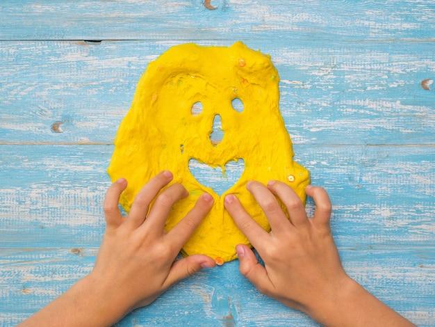 Het kind trekt een grappig gezicht van geel slijm op een blauwe tafel. antistress voor speelgoed. speelgoed voor de ontwikkeling van handmotoriek.
