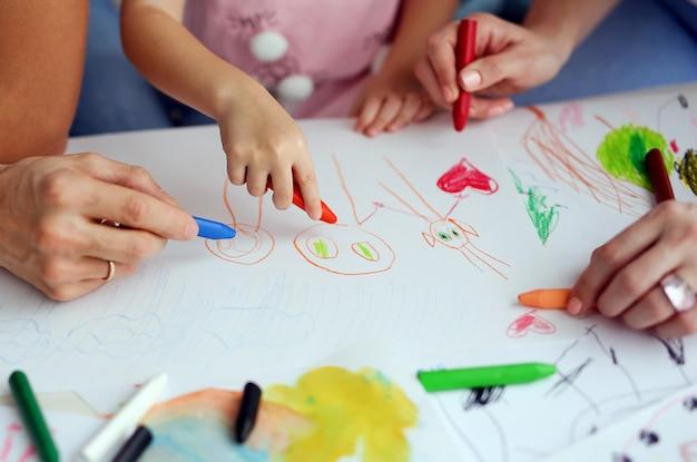 Het kind trekt een potloodtekening van gelukkige familie. ouders helpen het kind om een foto te maken