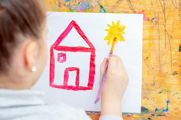 Het kind trekt gele zon met rood huis.