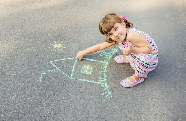 Het kind trekt het huis met krijt op het asfalt. selectieve aandacht.