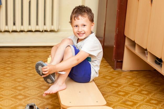 Het kind trekt schoenen aan in de kleuterschool