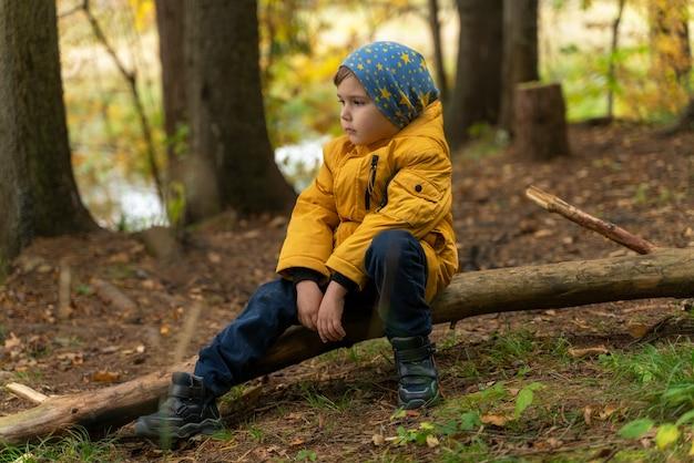 Het kind verkent het bos en ging zitten om uit te rusten
