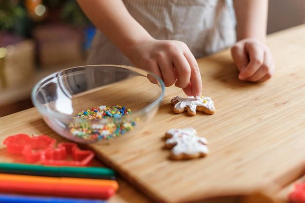 Het kind versiert peperkoek kerstkoekjes op een houten tafel.
