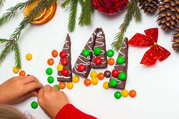 Het kind versiert wafels in de vorm van een kerstboom met gekleurde snoepjes kerstvoedsel