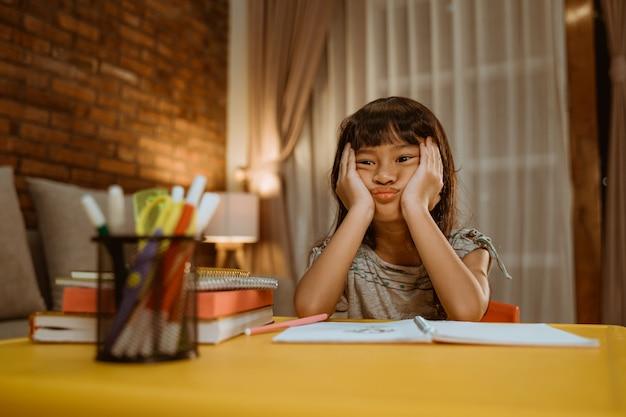 Het kind verveelt zich terwijl ze haar huiswerk maakt