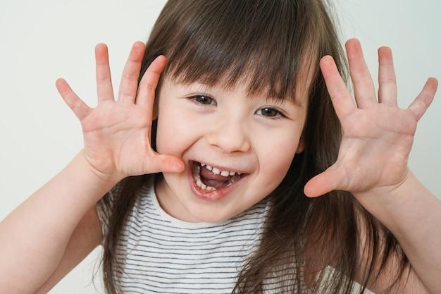 Het kind verwent zich. close-upportret van een vrolijk meisje. meisje zegt boe-geroep.