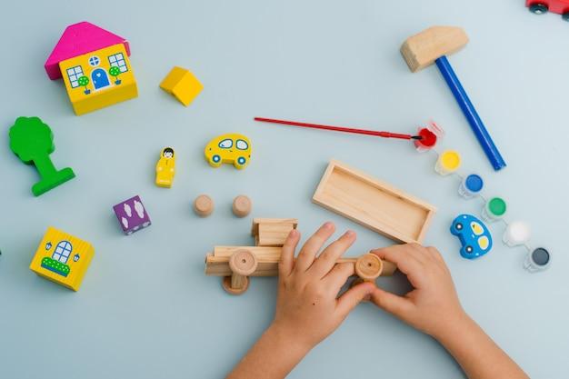 Het kind verzamelt en schildert een model van een typemachine gemaakt van hout