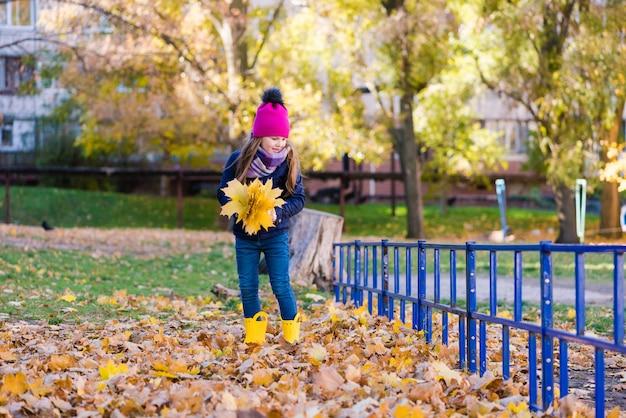 Het kind verzamelt gele bladeren tijdens een wandeling buiten