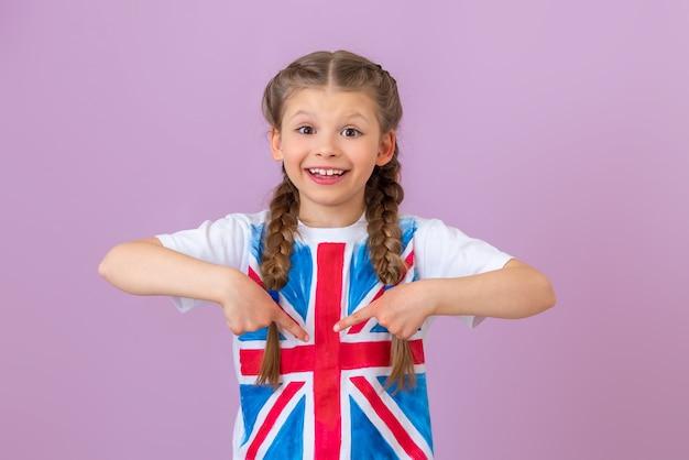 Het kind wijst met zijn vingers naar de geschilderde engelse vlag op zijn t-shirt.