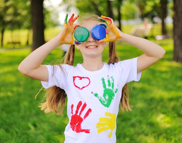 Het kind wordt besmeurd met felgekleurde vingerverven kleren glimlachend in het park.