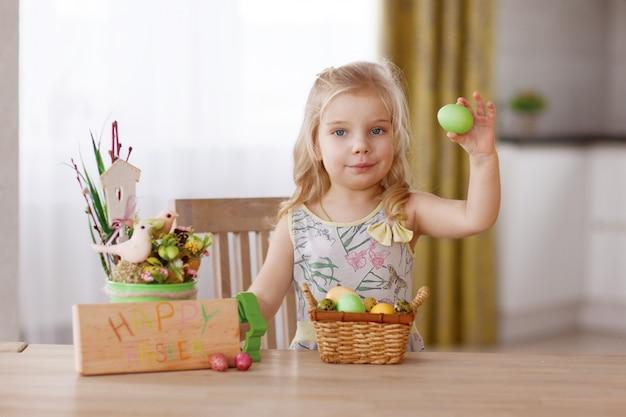 Het kind zit aan de vakantietafel met een mand met paaseieren. houdt een ei in zijn hand en denkt na