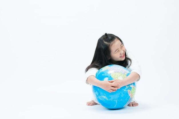 Het kind zit en glimlacht in het wit. de uitdrukking is een gelukkige glimlach.