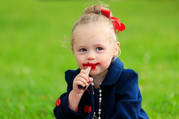 Het kind zit en schildert zijn lippen met rode lippenstift