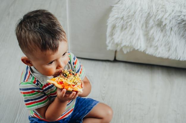 Het kind zit op de grond en eet pizza erg smakelijk en hebzuchtig, in korte broek en een t-shirt