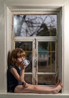Het kind zit op een armoedige houten vensterbank en drinkt uit een mok