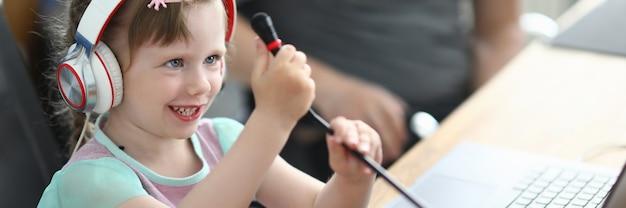 Het kind zit op stoel met hoofdtelefoons en houdt microfoon met zijn handen vast.