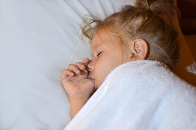 Het kind zuigt een vinger in bed voordat het naar bed gaat en tijdens de slaap