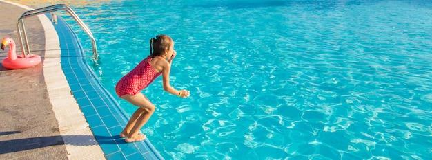 Het kind zwemt en duikt in het zwembad.