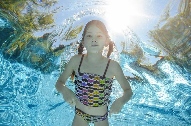 Het kind zwemt onderwater in zwembad, gelukkig actief tienermeisje duikt en heeft pret onder water