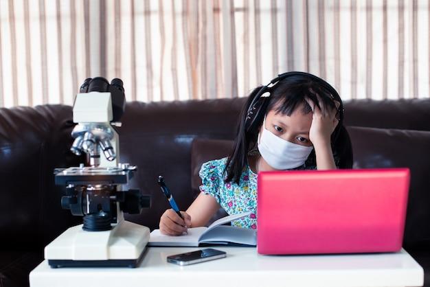Het kindmeisje die van de spanning gezichtsmasker en hoofdtelefoons dragen die online leren door laptop en microscoop thuis, afstandsonderwijs te gebruiken
