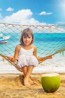 Het kindmeisje drinkt kokosnoot op het strand