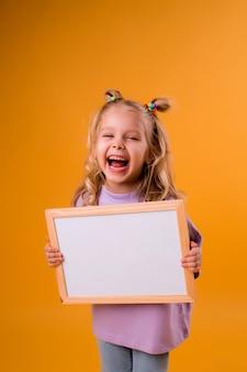 Het kindmeisje houdt een wit leeg tekenbord in haar handen