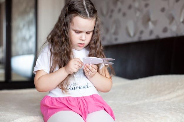 Het kindmeisje naait een stuk speelgoed gemaakt van vilt zittend op het bed op een beige deken; handwerk