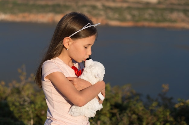 Het kindmeisje omhelst zacht stuk speelgoed beer