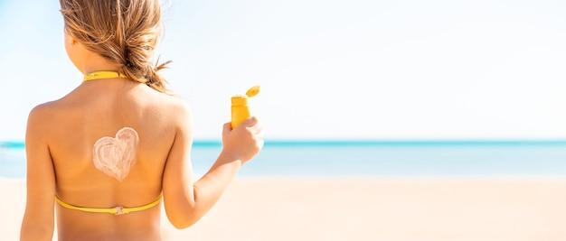 Het kindmeisje smeert zonnebrandcrème op haar gezicht