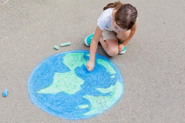 Het kindmeisje tekent een planeet, wereldbol met een wereldkaart met krijt op het asfalt.